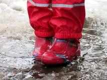 Das Kind, das für Pfützen auf den Straßen springt, tauen am Ende des Winters auf Lizenzfreie Stockfotografie