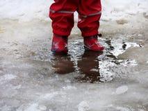 Das Kind, das für Pfützen auf den Straßen springt, tauen am Ende des Winters auf Stockbilder