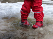 Das Kind, das für Pfützen auf den Straßen springt, tauen am Ende des Winters auf Stockfoto