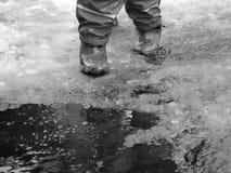 Das Kind, das für Pfützen auf den Straßen springt, tauen am Ende des Winters auf Lizenzfreies Stockfoto