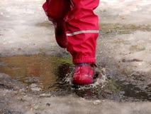 Das Kind, das für Pfützen auf den Straßen springt, tauen am Ende des Winters auf Stockfotos