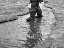 Das Kind, das für Pfützen auf den Straßen springt, tauen am Ende des Winters auf Lizenzfreie Stockbilder