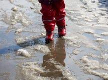 Das Kind, das für Pfützen auf den Straßen springt, tauen am Ende des Winters auf Lizenzfreies Stockbild