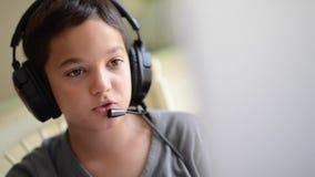 Das Kind, das glücklich ist, hören Musik und spielend auf dem Computer mit Kopfhörern den im Freien stock video footage