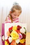 Das Kind, das Mädchen öffnet ein Geschenk Stockbild
