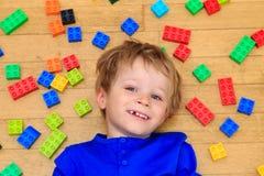 Das Kind, das mit buntem Plastik spielt, blockiert Innen Lizenzfreies Stockbild