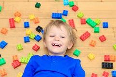 Das Kind, das mit buntem Plastik spielt, blockiert Innen Lizenzfreie Stockbilder