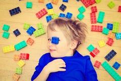 Das Kind, das mit buntem Plastik spielt, blockiert Innen Lizenzfreie Stockfotos