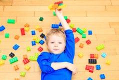 Das Kind, das mit buntem Plastik spielt, blockiert Innen Stockfoto
