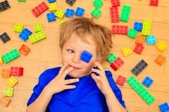 Das Kind, das mit buntem Plastik spielt, blockiert Innen Stockfotografie