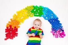 Das Kind, das mit Regenbogenplastik spielt, blockiert Spielzeug Stockbild