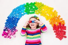 Das Kind, das mit Regenbogenplastik spielt, blockiert Spielzeug Stockfoto
