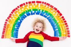 Das Kind, das mit Regenbogenplastik spielt, blockiert Spielzeug Stockfotografie