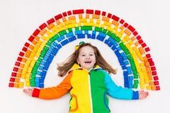 Das Kind, das mit Regenbogenplastik spielt, blockiert Spielzeug Lizenzfreies Stockfoto