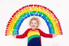 Das Kind, das mit Regenbogenplastik spielt, blockiert Spielzeug Lizenzfreie Stockfotografie