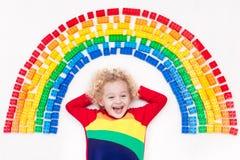 Das Kind, das mit Regenbogenplastik spielt, blockiert Spielzeug Lizenzfreie Stockbilder