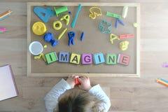 Das Kind, das sich auf dem Boden spielt mit einigen Würfelbuchstaben verfassen das Wort hinlegt, STELLEN sich vor Lizenzfreie Stockbilder