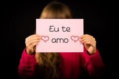 Das Kind, das Zeichen mit Portugiesen hält, fasst Eu Te Amo - ich liebe dich ab Stockbild