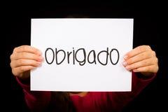 Das Kind, das Zeichen mit portugiesischem Wort Obrigado hält - danke Stockfotografie