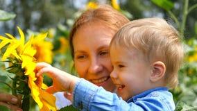 Das Kind in den Armen seiner Mutter, die mit Blume spielen Lizenzfreie Stockfotos