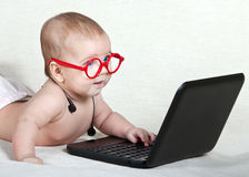 Das Kind in den Gläsern mit den Kopfhörern auf dem Hals, der die Laptopanzeige betrachtet lizenzfreies stockfoto