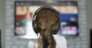 Das Kind in den Kopfhörern schaltet die Kanäle mit der Fernbedienung stock video