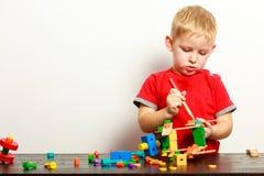 Das Kind des kleinen Jungen, das mit Bausteinen spielt, spielt Innenraum Lizenzfreie Stockbilder