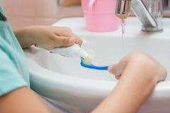 Das Kind drückt die Zahnpasta von einem Rohr auf Zahnbürste zusammen stockbilder