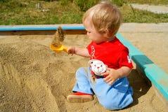 Das Kind in einem Sandkasten Lizenzfreies Stockfoto