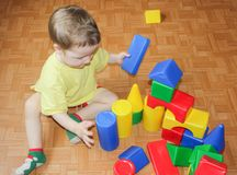 Das Kind errichtet ein Schloss aus Plastikdesigner heraus Ein kleiner Junge Stockbild