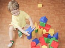Das Kind errichtet ein Schloss aus Plastikdesigner heraus Ein kleiner Junge Stockfoto