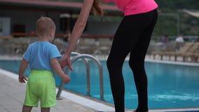 Das Kind geht zum Pool und reist vorsichtig von ihm in der Zeitlupe ab stock footage