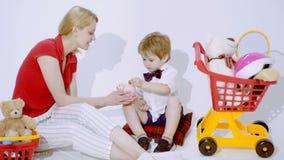 Das Kind, das Geld zählt und setzt sie in das Sparschwein Stecken eines Geldes in eine piggy Querneigung Kinderbetreuung Kinderer stock footage