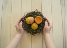 Das Kind hält das braune Ei mit einem Muster Gemalte braune Eier Lizenzfreie Stockfotos