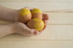 Das Kind hält das braune Ei mit einem Muster Gemalte braune Eier Lizenzfreies Stockfoto