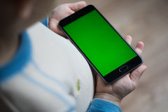 Das Kind hält ein Telefon in seiner Hand mit einem grünen Schirm für stockbilder