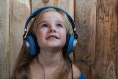 Das Kind hört auf Musikkinderhölzernen Hintergrund hörend Musik lizenzfreie stockfotos