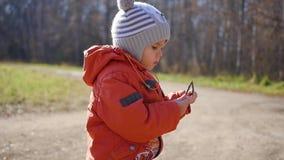 Das Kind, das in Herbst Park geht Ein Junge steht mit einem Stock in seinen Händen stock footage