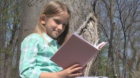Das Kind, das im Baum-Park liest, Schulmädchen liest das Buch, das in der Natur im Freien ist, Erziehungs stockfotografie
