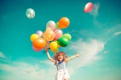 Das Kind im Frühjahr springend mit Feld der Spielzeugballone Stockfoto