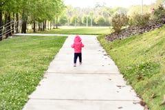 Das Kind, das im hohen Gras auf einem sonniger Tag-outsideA kleinen Mädchen steht, geht entlang den Weg an einem Park Lizenzfreie Stockfotografie