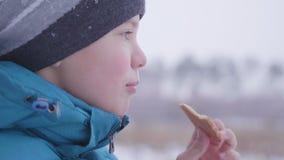 Das Kind isst den Plätzchenwinter im Freien Lizenzfreies Stockbild