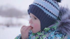 Das Kind isst den Plätzchenwinter im Freien Lizenzfreie Stockfotos