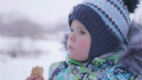 Das Kind isst den Plätzchenwinter im Freien Stockfotos