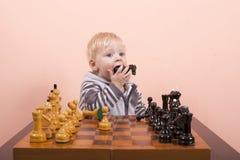 Das Kind isst Schach Lizenzfreie Stockfotos