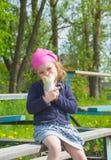 Das Kind isst Schnellimbiß auf der Straße an einem sonnigen Tag Stockfotos