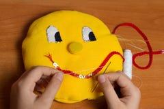 Das Kind lebt in einem weichen Spielzeug in Form einer gelben Sonne Stockfotografie