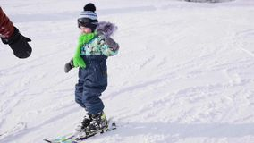 Das Kind lernt, mit einem Lehrer Ski zu fahren Makro des grünen Grases Aktiver Sport stock footage