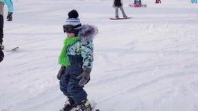 Das Kind lernt, mit einem Lehrer Ski zu fahren Makro des grünen Grases Aktiver Sport stock video