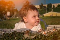 Das Kind liegt auf dem Gras stockfotos
